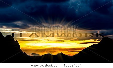Teamwork concept mountain peak with teamwork text and beautiful sky and sunray