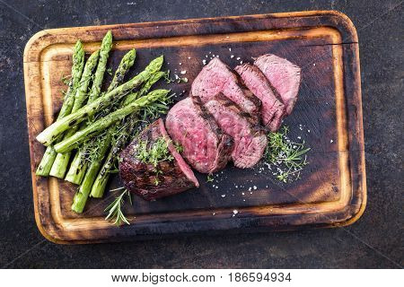 Barbecue Wagyu Point Steak with green Asparagus as close-up on burnt cutting board