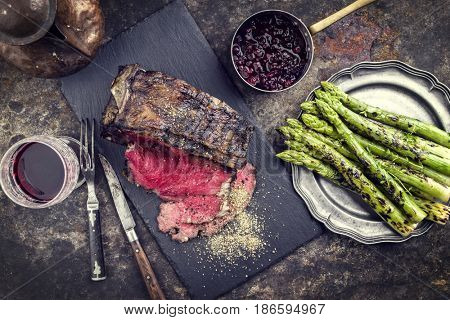 Barbecue dry aged Rib of Beef with green Asparagus and Cranberries as close-up on an old metal sheet