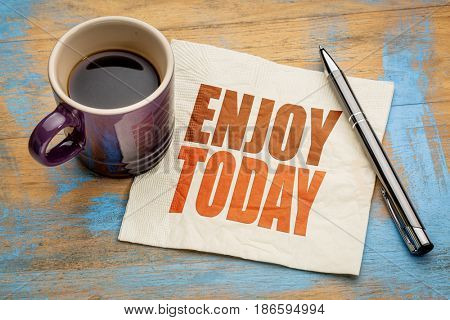 Enjoy today inspirational word abstract  on a napkin with a cup of espresso coffee
