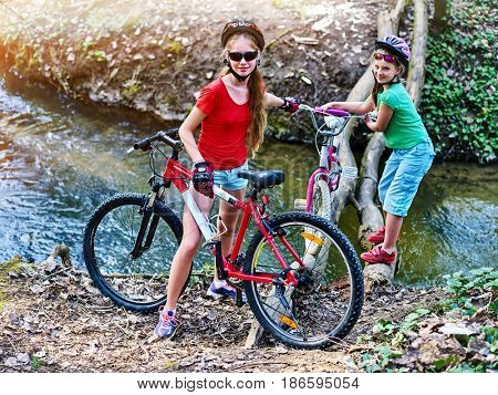 Bicycle teen with ladies bikes in summer park. Womens road bike for running on nature. Teenager girl in helmet cycling fording throught water. Brave children are not afraid to travel unaccompanied.