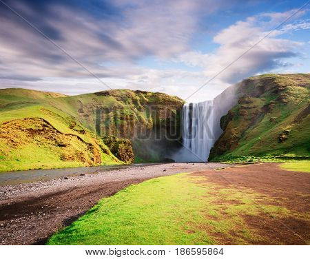 Skogafoss waterfall and Skoga river. Famous landmark of Iceland. Summer landscape on a sunny day. Amazing in nature