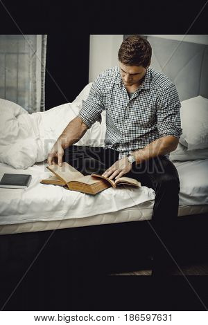 Man reading a book in his bed.