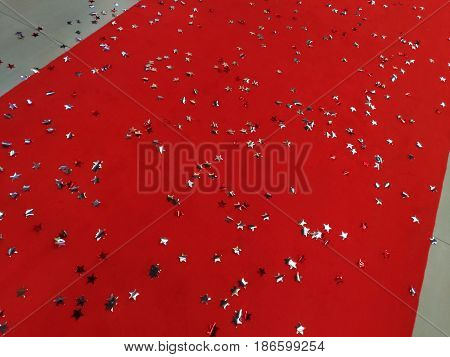 The red carpet is dotted with shiny gray stars. Red fabric on the floor of tiles, silver sprockets of foil. Concept: holiday decoration of the event,