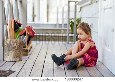 Female Pupil At Montessori School Putting On Wellington Boots