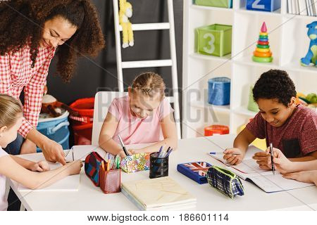 Smiling children drawing during art class with teacher