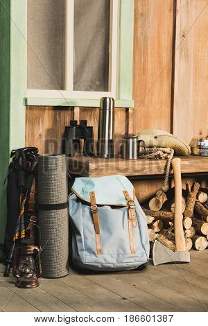 Different Trekking Equipment On Bench Near Wooden House Waiting For Traveler