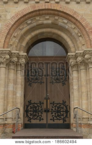 Beautiful large wooden doors with forging in the arch in neoromansky style architecture