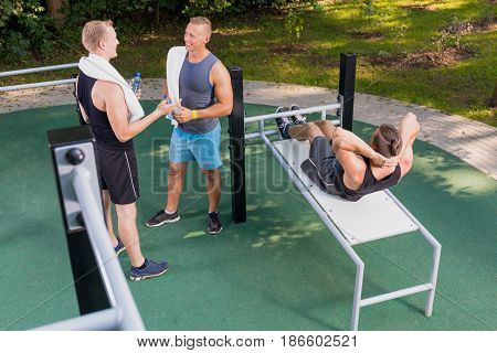 Man Doing Sit-ups And His Friends Resting