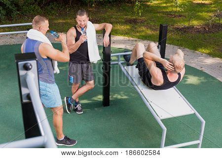 Man Doing Sit-ups And His Friends Drinking Water