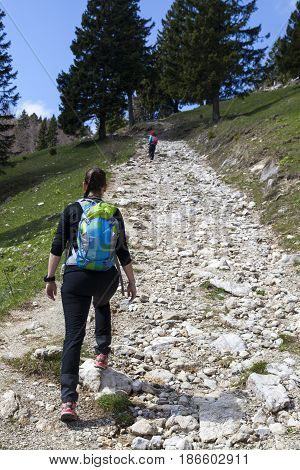 Hikers walking on hike in mountain nature landscape in Slovenian Alps. Hiking - sporty hiker woman on trek with backpack living healthy active lifestyle