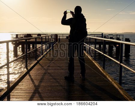 Man On Mole Takes Pictures Of Spring  Morning At Sea
