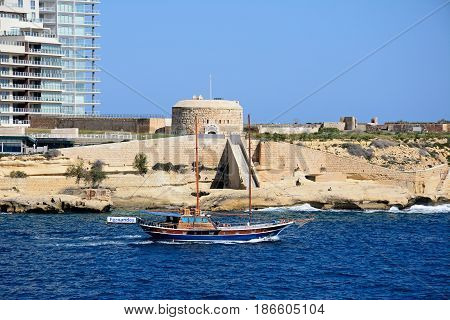 VALLETTA, MALTA - MARCH 30, 2017 - View of Fort Tigne with a wooden ship in the foreground seen from Valletta Sliema Malta Europe, March 30, 2017.