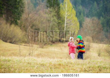 Happy two kids holding hands in mountain landscape in nature in spring season