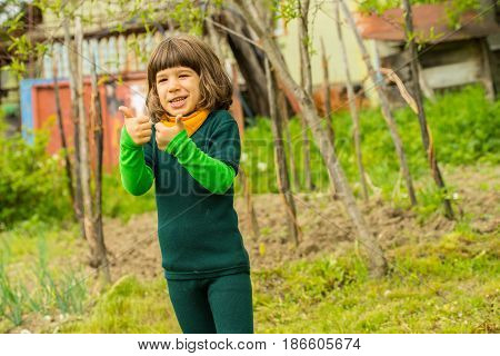 Cheerful boy in garden giving thumbs and smiling