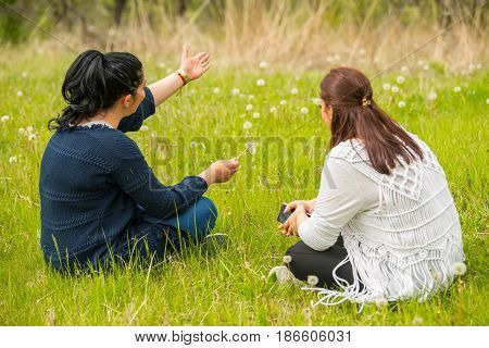 Two women having conversation in nature and brunette woman showing something to hills