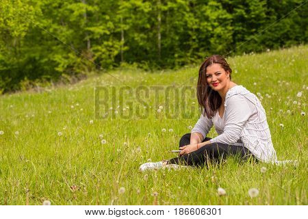 Woman in nature sitting in grass with dandelion seeds around her