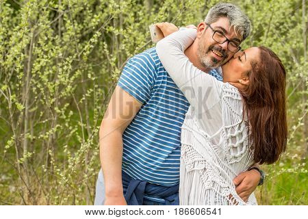 Happy couple of man and woman embracing and kissing in front of forest in nature