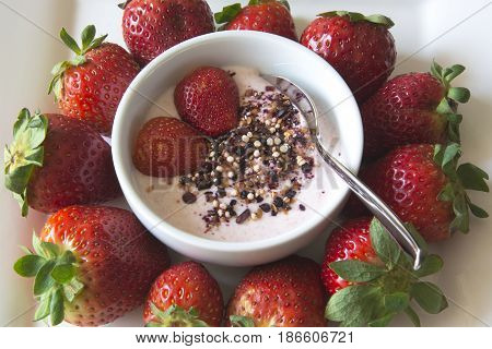 Greek strawberry yoghurt served in a bowl with strawberries and a superfruit topping of dried blueberries, hibiscus, chia seeds and airy quinoa pops