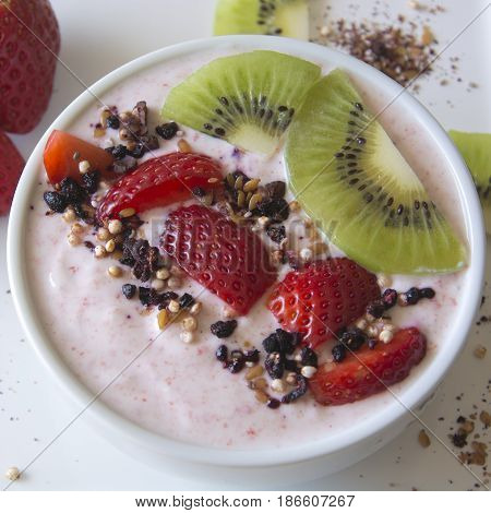 Greek strawberry yoghurt served in a bowl with fresh strawberries, kiwis and a superfruit topping of dried blueberries, hibiscus, chia seeds and airy quinoa pops