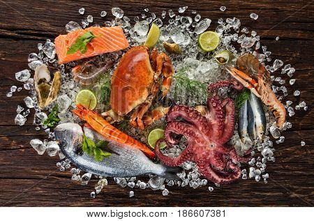 Fresh seafood, crab, mussels, prawns, fish, crab, salmon steak, bream fish and other shells served on old wooden table