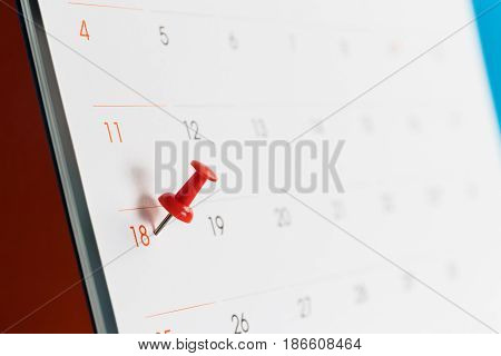 Close up red pin on white calendar.