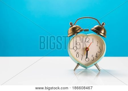 Heart Alarm Clock On White Table And Blue Wall Background. Valentine's Day Background