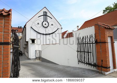 Sundial on building. Kaunas, Lithuania - May 15, 2017: Sundial: A Smiling City Symbol. The ever-happy sundial in the Old Town of Kaunas was installed in 1986 on the wall of Vilnius University.