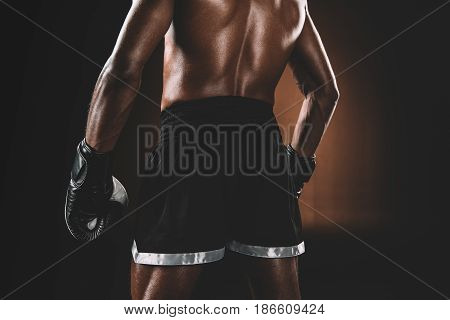 Back View Of Shirtless Muay Thai Athlete Standing In Studio, Boxing Gloves Fight Concept