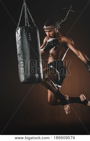 Concentrated Young Sportsman Jumping And Thai Boxing With Punching Bag, Boxing Gloves Fight Concept