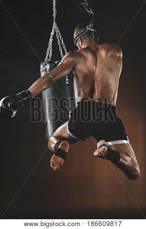 Back View Of Muay Thai Fighter Training With Punching Bag, Action Sport Concept