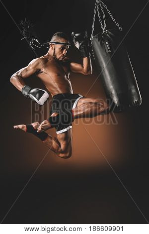 Side View Of Concentrated Muay Thai Fighter Training With Punching Bag, Action Sport Concept