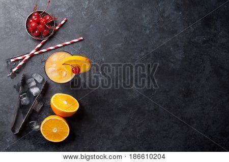 Tequila sunrise cocktail on dark stone table. Top view with space for your text