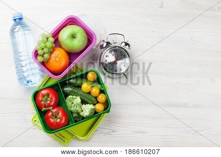 Lunch box with vegetable and fruits on wooden table. Top view with copy space