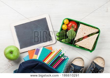 Lunch box with vegetables and sandwich on wooden table. Kids take away food box and school supplies. Top view with chalkboard for your text