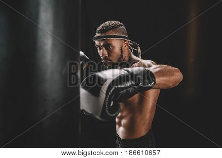 Portrait Of Focused Muay Thai Fighter Practicing Punch On Punching Bag