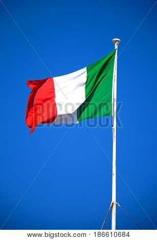 Italian Flag against a blue sky on top of the main guard building in St Georges Square Valletta Malta Europe.