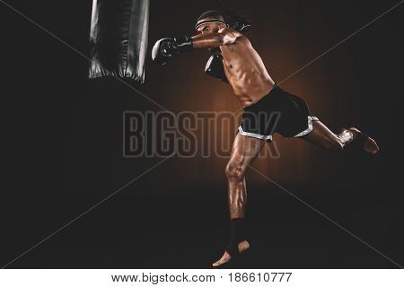 Side View Of Muay Thai Fighter Training With Punching Bag, Action Sport Concept