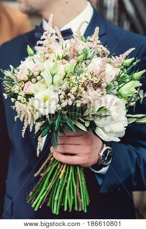 fiance in a dark blue suit hold in hands a wedding bouquet made of white flowers