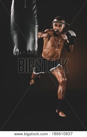 Angry Muay Thai Fighter Practicing Punch On Punching Bag, Action Sport Concept