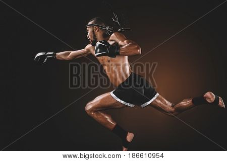Side View Of Muay Thai Fighter In Boxing Gloves Practicing Punch, Action Sport Concept