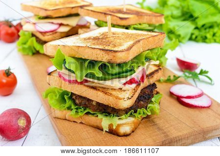 Multilayered sandwiches with a juicy cutlet cheese radish cucumber lettuce arugula on a cutting board on a white wooden background.