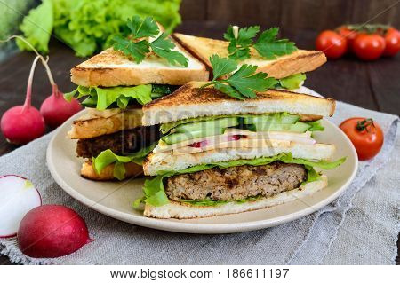 Multilayered sandwiches with a juicy cutlet cheese radish cucumber lettuce arugula cutting in half on a plate on a dark wooden background.
