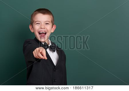 school boy point the finger near blank chalkboard background, dressed in classic black suit, group pupil, education concept