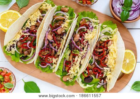 Tacos is a traditional Mexican dish. Tortilla stuffed with chicken bell and hot peppers beans lettuce cheese blue onion with salsa sauce on white wooden background. Top view. Close up
