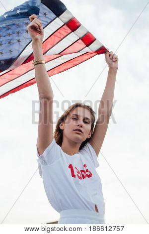 Young caucassian woman holds up american flag high up in the sky with pride and joy