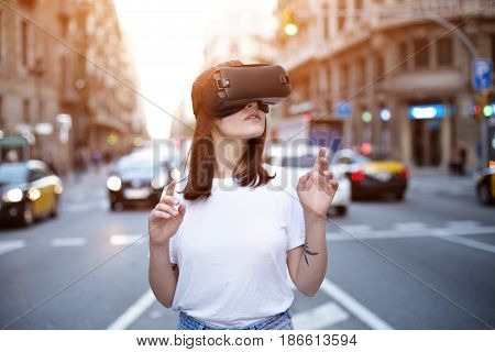 Handsome petite female back end developer explores exciting and thrilling world of augmented virtual reality in the middle of a busy multi cultural city