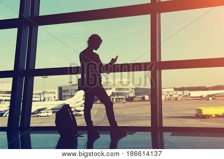 businesswoman at the airport. silhouette of a girl with mobile phone and backpack. business and travel