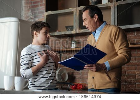 It is me. Delighted male person standing opposite his son while speaking to him and holding his copybook