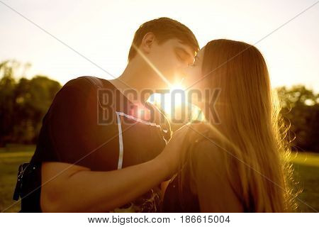 Kiss of a loving couple at sunset.